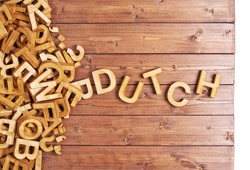 Word dutch made with block wooden letters next to a pile of other letters over the wooden board surface composition