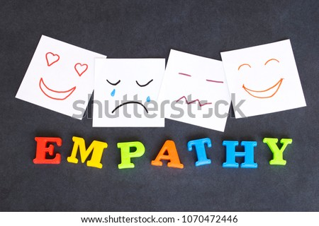 Word Empathy made of colorful letters and funny faces drawn on notes on the dark background.