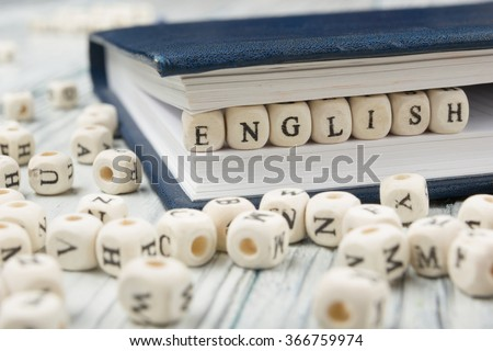 Word english made with block wood letters next to a pile of other letter over  wooden table