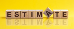 Word ESTIMATE is made of wooden building blocks lying on the table and on a light yellow background. Concept