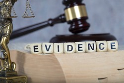 Word EVIDENCE composed of wooden letters. Statue of Themis and judge's gavel  in the background