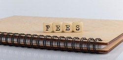 word FEES made with letters on wooden blocks on the wooden notepad