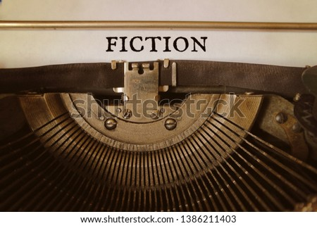 Word fiction is typed by an old typewriter on a paper.