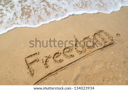 Word FREEDOM on the beach.
