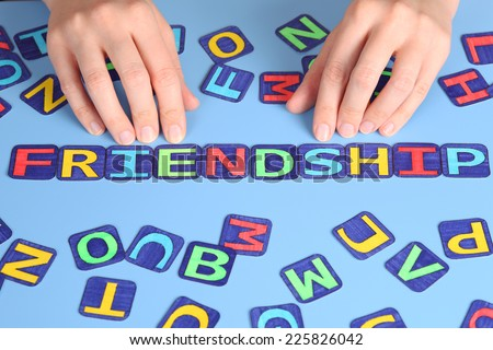 Word Friendship spell out on a desk with woman\'s hands and letters. Letters draw by myself.