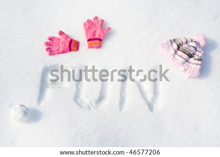 "Word ""FUN"" written on fresh snow, with pink gloves, cap and snowball."