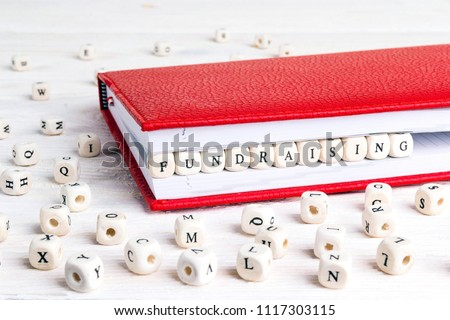Word Fundraising written in wooden blocks in red notebook on white wooden table. Wooden abc. #1117303115