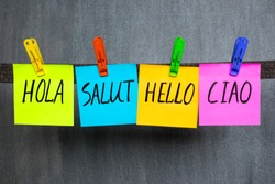 Word Hello in different languages written on colorful notes on the dark background.