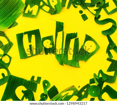 Word HELLO letters from green tropical palm leaves on yellow textured background. Original handmade idea from natural material for summer design and needlework #1298943217