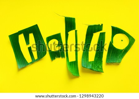 Word HELLO letters from green tropical palm leaves on yellow textured background. Original idea from natural material for summer design #1298943220
