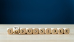 Word impossible spelled on wooden dices with the second one turning to spell the Its possible sign.