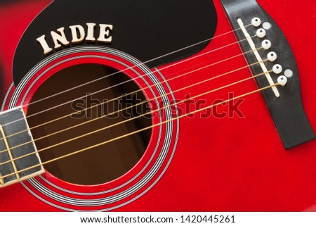 Word Indie with wooden letters, closeup on a surface of red acoustic guitar. Music entertainment background. #1420445261