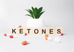 Word KETONES made from wooden letters on grey backgound. Plant on backgound. Medical concept