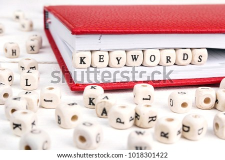 Word Keywords written in wooden blocks in red notebook on white wooden table. Wooden abc.