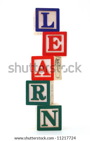 word learn formed by alphabet wood blocks over a white surface