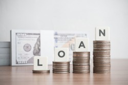 Word LOAN on step stack coins as graph up with banknotes background. Business and finance concept. Interest and fees from loans are main revenue for banks. Loans can be unsecured such as credit card.