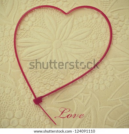 word love and a heart-shaped zip tie on a flower patterned background