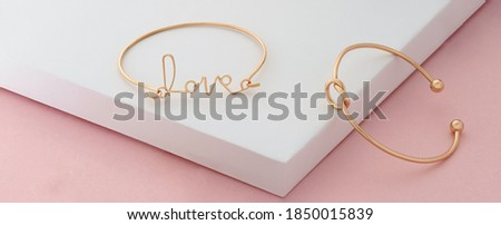 Word love and knot shape golden bracelets on pink and white background Foto stock ©