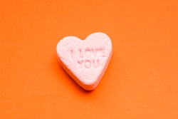 Word love in English on a candy heart, sweet image for Valentine's Day, isolated on red background.