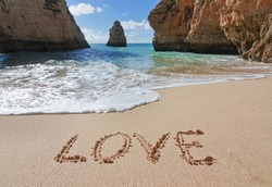 Word love in the sand at the beach on Valentine Day.