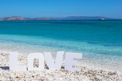 Word love on tropical beach background of the turquoise sea and blue sky