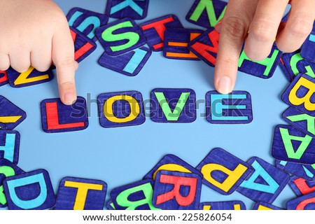 Word Love spell out on the desk with child\'s and mother\'s hands and letters. Letters drawn by me.