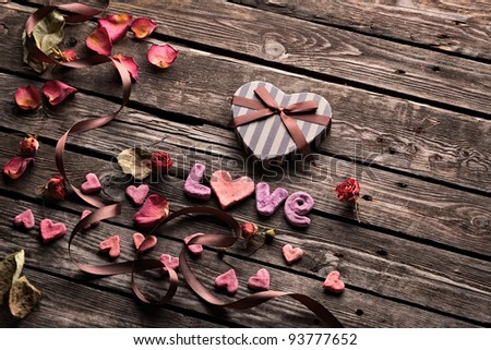 Word Love with Heart shaped Valentines Day gift box on old vintage wooden plates. Sweet holiday background with rose petals, small hearts, curved ribbon.