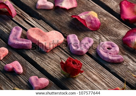 Word Love with rose petals and small heart shaped stuff closeup on old vintage wood plates. Sweet holiday background.