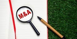 Word M and A - mergers and acquisition written on notebook red letters. Conceptual photo. Top view