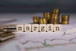 Word MARGIN  composed of wooden letter. Stacks of coins in the background. Closeup
