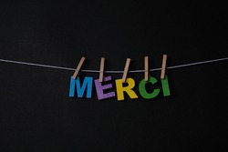 Word Merci on black background. Merci is the most common way to say thank you or thanks in French.