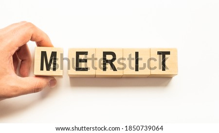 Word merit. Wooden small cubes with letters isolated on white background with copy space available.Business concept Stockfoto ©