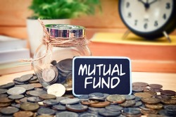 Word Mutual Fund on mini chalkboard and coin in the jar with blurred background of books, green plant and clock. Financial Concept.