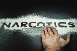 Word NARCOTICS reflected on white powder imitating drugs. Concept of health and medicine. Problems and drug addiction. The NARCOTICS inscription smeared with the hand.
