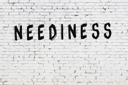 Word neediness written with black paint on white brick wall.