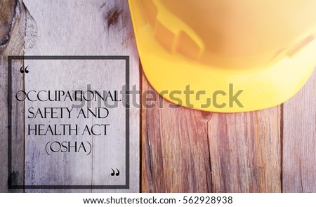 Word OCCUPATIONAL SAFETY AND HEALTH ACT (OSHA) with yellow safety helmet on wooden base