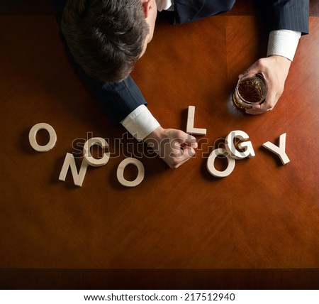 Word Oncology made of wooden block letters and devastated middle aged caucasian man in a black suit sitting at the table with the glass of whiskey, top view composition with dramatic lighting