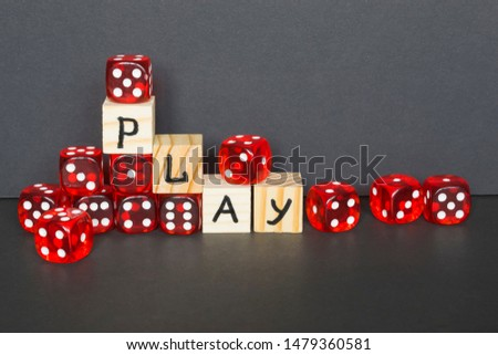 Word Play written on wooden cubes and red dice on the dark background.  #1479360581