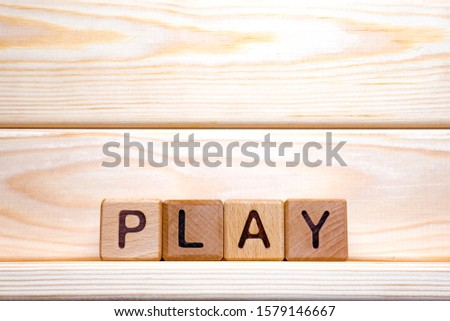 Word play written on wooden cubes on wooden background. Wooden cubes formed the word play. Online, dramatic play. For wood latin letters made the word play
