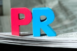 Word PR on newspaper. Wooden letters. Public Relations concept.