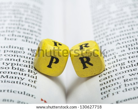 Word PR.Wooden cubes on newspaper. Close up studio shot - stock photo
