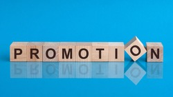 Word promotion is made of wooden building blocks lying on the table and on a light blue background. Promotion - word from wooden blocks with letters.