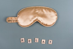 Word Relax and golden sleeping eye mask, top view. Good night, flight and travel concept. Sweet dreams, relax, siesta, insomnia, relaxation, tired, travel concept. Do not disturb, bedtime concept