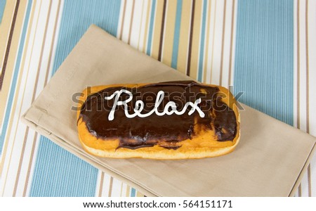 word relax written on chocolate long john donut on cloth napkin ストックフォト ©