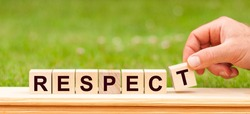 Word Respect written with wooden blocks. Man hand holding wooden cube block with Respect business word on green lawn background.