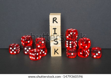 Word Risk written on wooden cubes and red dice on the dark background.  #1479360596