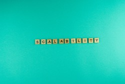 Word Scalability. The phrase is laid out in wooden letters. Top view. Motivation. Blue background. Copy space.