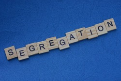 word segregation  made from  wooden letters lies on a blue table