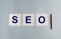 Word seo on white stickers and a golden pen on grey blue background