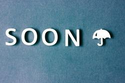 Word soon written on a blue background. Open umbrella against grey sky background. Autumn, fall time. Bad weather, storm, precipitation. Creative image of cold raining season. Minimalist wallpaper.